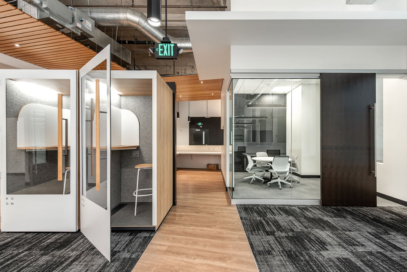 Office space interior showing rooms separated by glass and wood