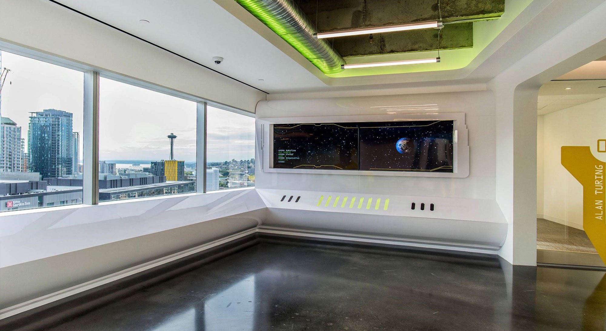 Axon office interior showing view of Space Needle and downtown Seattle. Interior has giant futuristic screen and florescent lighting
